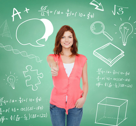 education, school, gesture and people concept - smiling teenage girl in casual clothes showing thumbs up over green board background photo