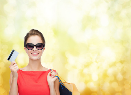 shopping, sale, christmas and holiday concept - smiling elegant woman in red dress with shopping bags and plastic card photo