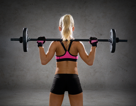 pumping: fitness, sport and dieting concept - sporty woman exercising with barbell from back over concrete wall background Stock Photo