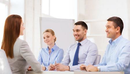 zaken, carrière en kantoorconcept - lachende zakenvrouw op sollicitatiegesprek in het kantoor