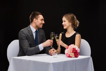 Glasses of champagne and candles: nhà hàng, cặp vợ chồng và kỳ nghỉ khái niệm - mỉm cười với cặp vợ chồng ly sâm banh nhìn nhau tại nhà hàng Kho ảnh