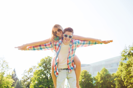 holidays, vacation, love and friendship concept - smiling couple having fun in park photo