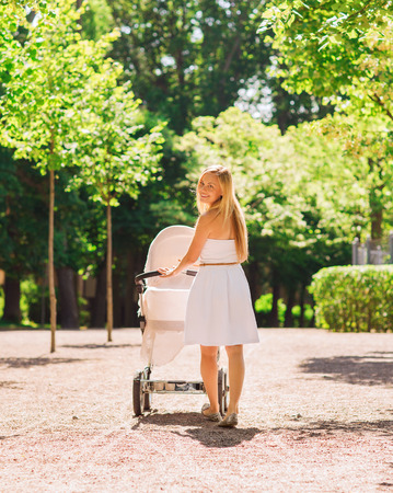 mothercare: family, child and parenthood concept - happy mother walking with baby stroller in park from back Stock Photo