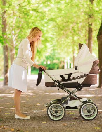 La familia, el niño y el concepto paternidad - madre feliz con el cochecito en el parque Foto de archivo - 31158853
