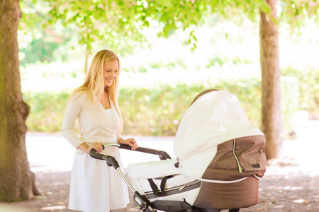 stroller: family, child and parenthood concept - happy mother with stroller in park