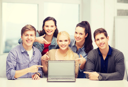 education, technology, advertisement and internet concept - group of smiling students pointing to blank black laptop screen photo