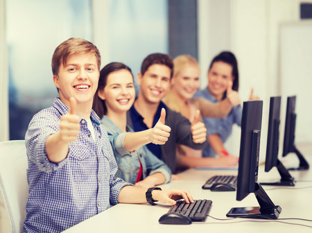 online learning: education, techology and internet concept - group of smiling students with computer monitor showing thumbs up at school