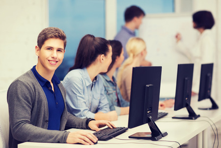 education, techology and internet concept - group of smiling students with computer monitor looking at teacher at school photo