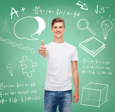 approvement: gesture, advertising, education, school and people concept - smiling young man in blank white t-shirt showing thumbs up over green board background with doodles Stock Photo