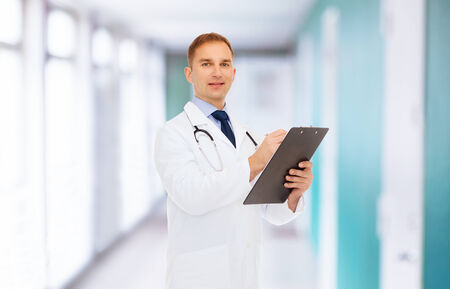 medicine, profession and healthcare concept - smiling male doctor with clipboard and stethoscope writing prescription over hospital background photo