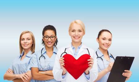 heart doctor: healthcare and medicine concept - smiling female doctor and nurses with red heart