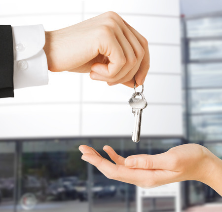real estate concept - picture of man hand passing house keys to woman Stock Photo