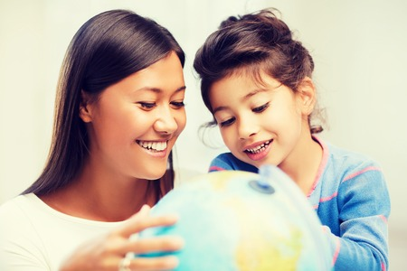 family, children, education, school and happy people concept - mother and daughter with globe photo