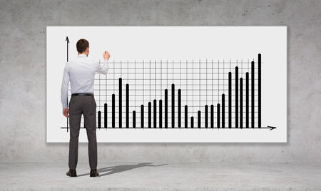business, development and office people concept - businessman with marker drawing chart over concrete wall background from back photo