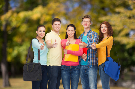 friendship, vacation, education, gesture and people concept - group of smiling teenagers with folders and school bags showing thumbs up over park background photo