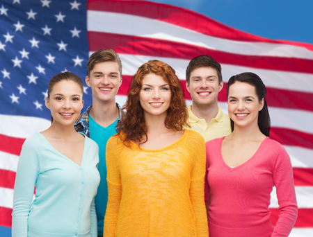 friendship, patriotism and people concept - group of smiling teenagers standing over american flag background photo
