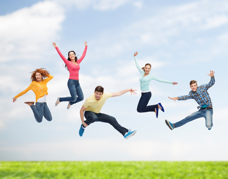 happiness, freedom, friendship, summer and people concept - group of smiling teenagers in air over natural background photo