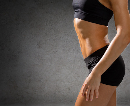six girls: fitness, sport and people concept - close up of beautiful athletic female abs in sportswear over concrete wall background