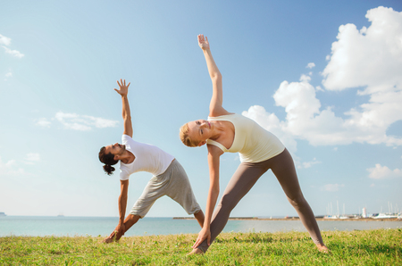 fitness, sport, friendship and lifestyle concept - smiling couple making yoga exercises outdoors photo