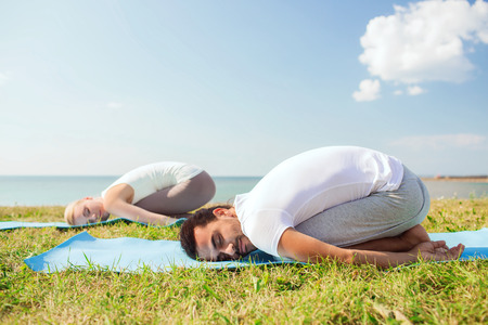 fitness, sport, friendship and lifestyle concept - smiling couple making yoga exercises on mats outdoors photo
