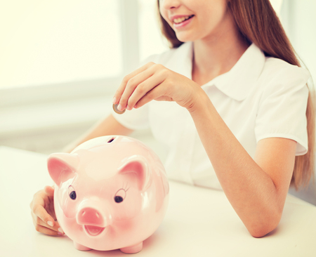 education, school and money saving concept - smiling child putting coin into big piggy bank photo