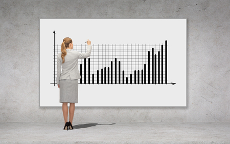 business, development and office people concept - businesswoman with marker drawing chart over concrete wall background from back photo