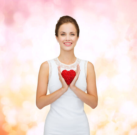 happiness, health, charity and love concept - smiling woman in white dress with red heart over pink lights background photo