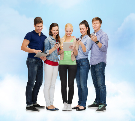 education and modern technology concept - smiling students using smartphones and tablet pc over blue sky background photo