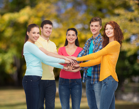 many hands: friendship, summer vacation, teamwork, gesture and people concept - group of smiling teenagers putting hand on top of each other over green park background