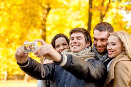parejas caminando: relación, la temporada, la amistad, la tecnología y el concepto de la gente - grupo de sonrientes hombres y mujeres haciendo el retrato de uno mismo con la cámara digital en el otoño de parque Foto de archivo