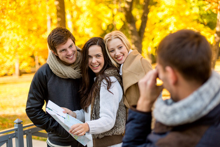 travel, people, tourism, photography and friendship concept - group of smiling friends with map taking picture in city park photo