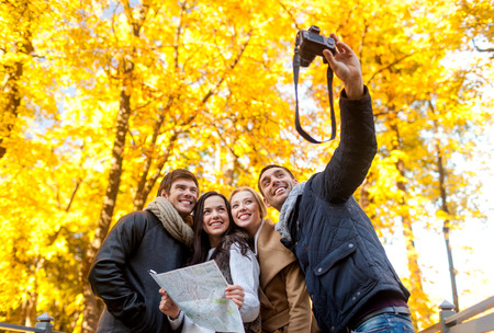travel, people, tourism, technology and friendship concept - group of smiling friends with map and camera making self portrait in city park photo