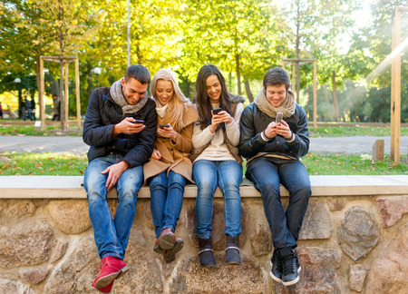 zellen: Reisen, Urlaub, Mensch, Technik und Freundschaft Konzept - Gruppe von Freunden l�chelnd mit Smartphones im Stadtpark Lizenzfreie Bilder
