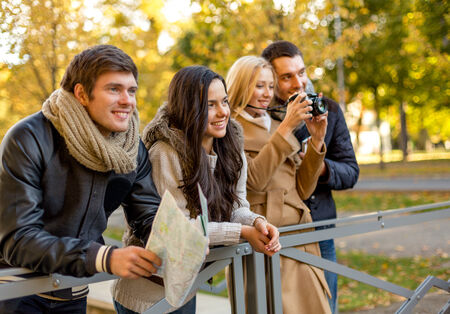 travel, vacation, technology, tourism and friendship concept - group of smiling friends with digital photo camera and map in city park photo