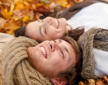 lying in leaves: love, relationship, season, family and people concept - close up of smiling couple lying in autumn park