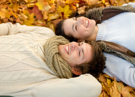 love, relationship, season, family and people concept - close up of smiling couple lying in autumn park