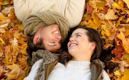 lying on leaves: love, relationship, season, family and people concept - close up of smiling couple lying in autumn park