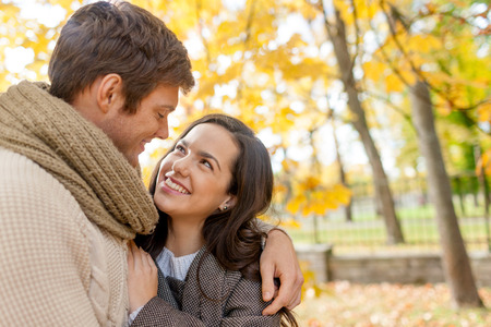recien casados: amor, las relaciones, la familia y las personas concepto - sonriente pareja abrazando en Parque de oto�o Foto de archivo