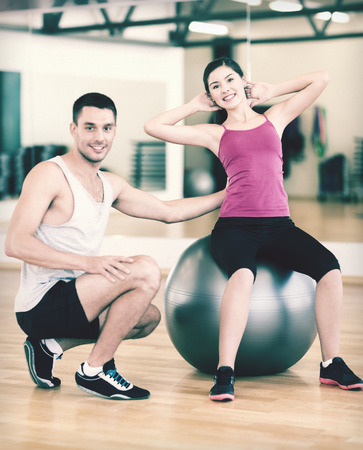 fitness, sport, training, gym and lifestyle concept - male trainer with woman doing crunches on the ball Stock Photo