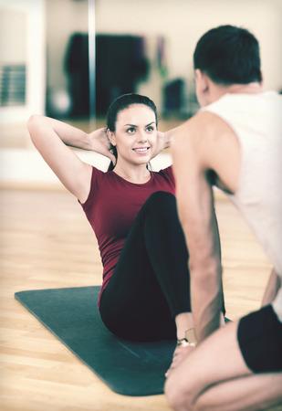 fitness, deporte, entrenamiento, gimnasio y estilo de vida concepto - entrenador masculino con mujer haciendo abdominales