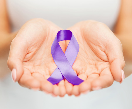 heal sickness: healthcare and social problems concept - womans hands holding purple domestic violence awareness ribbon Stock Photo