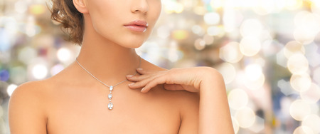 jewelry: wedding, bridal, jewelry and luxury concept - beautiful woman wearing shiny diamond necklace