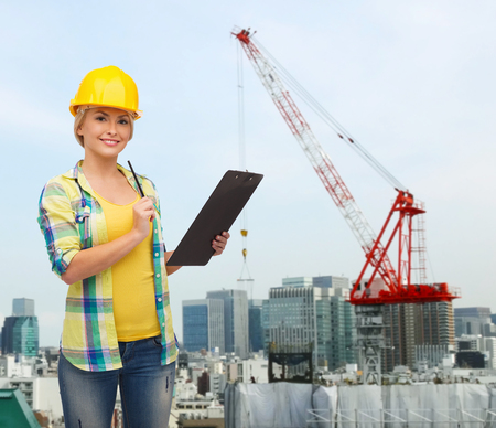repair, building, construction and maintenance concept - smiling woman in helmet with clipboard making notes photo