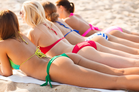 lying: summer vacation, holidays, travel and people concept - close up of young women lying on beach from back
