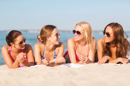 chilling: summer vacation, holidays, travel and people concept - group of smiling young women in sunglasses lying on beach