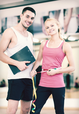 fitness, sport, training, diet and lifestyle concept - two smiling people with clipboard and measure tape in the gym photo