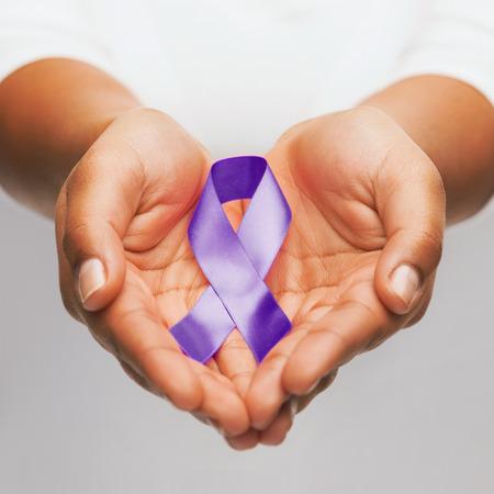 morado: cuidado de la salud y un problema social Concepto - womans manos sosteniendo conciencia cinta p�rpura violencia dom�stica Foto de archivo