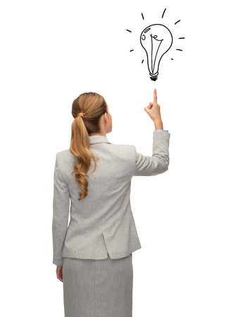 business, education, people and office concept - businesswoman or teacher in suit pointing finger up to bulb doodle from back over white background photo