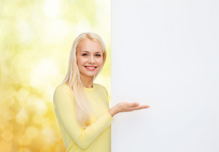 people, advertisement and sale concept - happy woman in sweater with blank white board photo