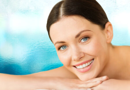 health and beauty, resort and relaxation concept - woman in spa salon lying on the massage desk photo